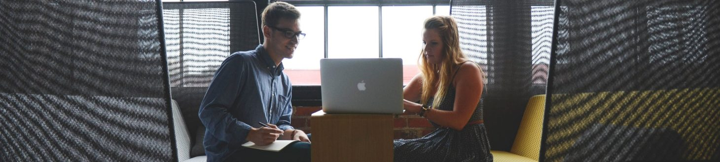 two people reading business reviews on a laptop