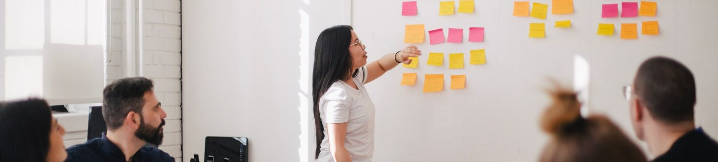 woman placing sticky notes on wall